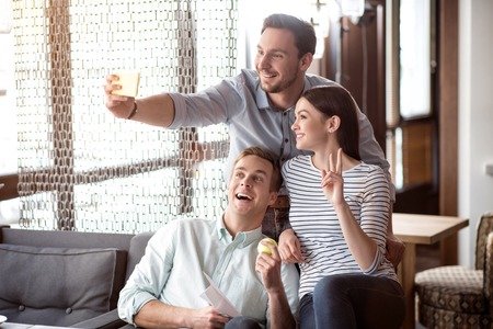 say cheese: Say cheese. Overjoyed delighted smiling friends sitting on the couch and expressing gladness while making selfie