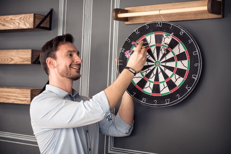 gladness: Relief negativity. Cheerful content handsome smiling man standing near the wall and expressing gladness while playing darts
