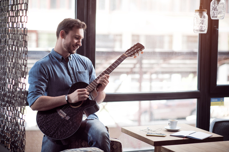 gladness: Like a real musician. Cheerful content smiling man leaning on the arm chair and playing the guitar while expressing gladness