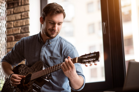 gladness: Feel the music. Positive handsome delighted man smiling and playing the guitar while expressing gladness