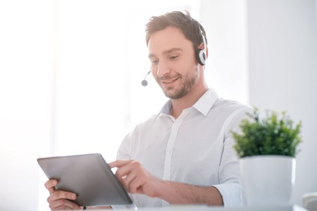 modern generation: Modern generation. Pleasant positive handsome smiling man sitting at the table and using headset with micro while working on the tablet