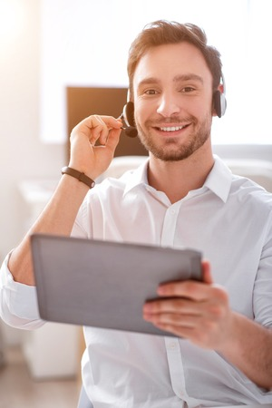gladness: Best professional.  Cheerful content smiling  man holding tablet and using headset with micro while expressing gladness Stock Photo
