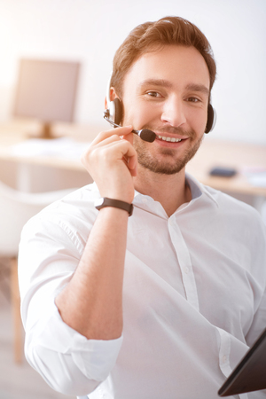 gladness: In connection. Positive content smiling  man holding tablet and using headset with micro while expressing gladness
