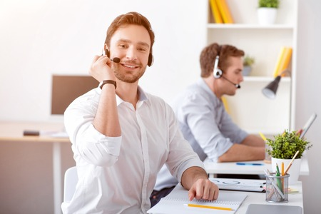 diligente: Diligent worker. Pleasant delighted handsome man using headset with micro and working in the call center while sitting at the table with his colleague