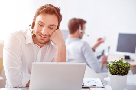 busy beard: Share positivity. Cheerful handsome smiling man talking with the help of headset with micro and using laptop while his colleague sitting at the table in the background