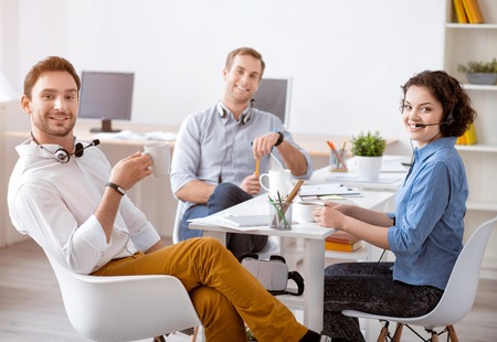 people relax: Work in concert. Cheerful content smiling colleagues sitting at the  table and having a break while drinking coffee