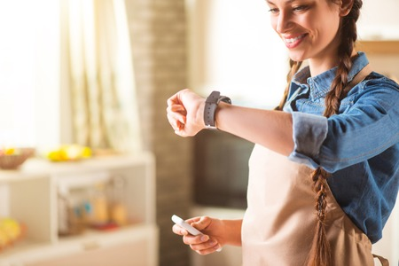 expressing joy: What time is it. Pleasant delighted beautiful smiling woman looking at her smart watch and expressing joy while standing in the kitchen