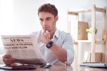 violence in the workplace: Spotlight. Pleasant handsome concentrated man sitting at the table and holding his hand on the chin while reading newspaper
