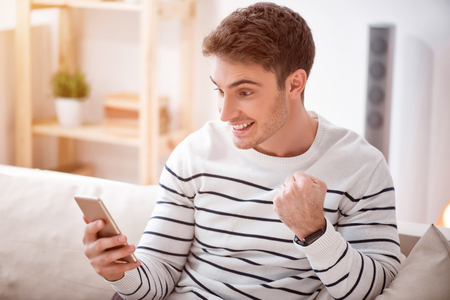 gladness: Taste of gladness. Cheerful positive smiling man sitting on the couch and holding cell phone while expressing joy