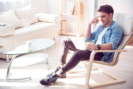 pleasant: Charged with fashion. Pleasant handsome delighted man sitting in the armchair and resting while using laptop