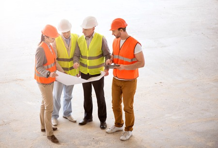 Consultation. A confident group of builders standing together, looking at plans with apprentices and talking about serious problems Stock Photo