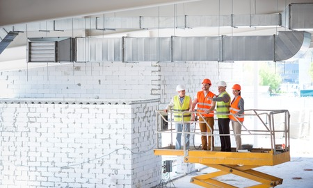 poking: High. A group of cheerful and smiling builders standing together at an elevator and poking somewhere