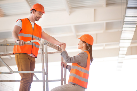 to go up: Helping hand. Cheerful worker in a hardhat helping a smiling woman to go up higher