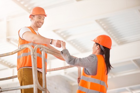 to go up: Gentleman. Generous man in a hardhat helping a cheerful woman to go up higher Stock Photo