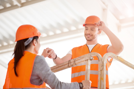 to go up: True gentleman. Smiling and delighted man in a hardhat helping content woman to go up higher Stock Photo