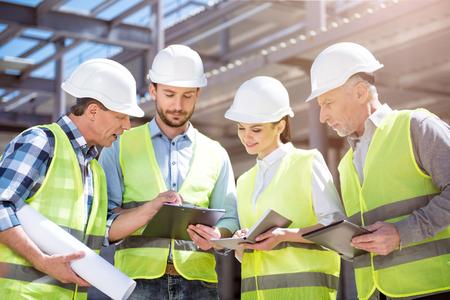 Het druk hebben. Een groep van de inhoud ingenieurs in hardhats staan samen in een nieuw gebouw en het werken tijdens het gebruik van een digitale tablet, plannen en verschillende kranten