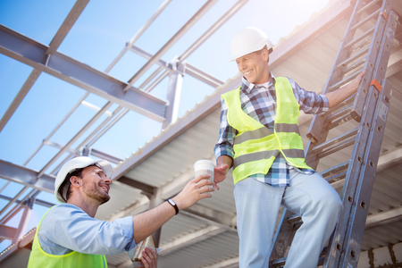 atmosphere construction: Friendly atmosphere.  Delighted and content worker giving a cup of strong coffee for another smiling worker, which being on stripes while construction Stock Photo