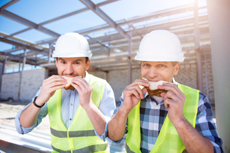 atmosphere construction: Hungry workers.  Angry and serious workers having lunch-hour and eating tasty sandwiches while being on construction