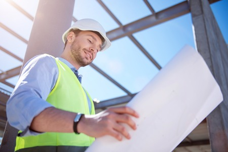 Planning of development. Young positive arhitect being on construction works and looking blueprints and building plans with a confident smile on his face Stock Photo