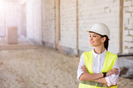 prospection: Looking into the future. Smiling and glad young female engineer being on construction works and thinking about future steps Stock Photo