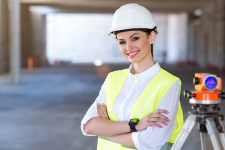 geodetic: Modernizing. Smiling and content young architect standing and looking at a camera with a geodetic level in a background Stock Photo