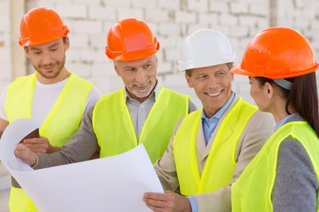 atmosphere construction: Pleasant working atmosphere. Smiling and cheerful positive group of engineers standing together, looking at a plan and discussing some details while being at construction works