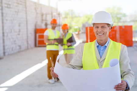 atmosphere construction: Passionate about work.  Smiling and happy architect standing and looking at a camera while holding a building plan with another content pair of engineers in a background
