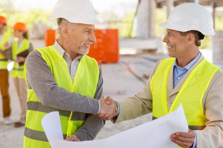 atmosphere construction: Coming to terms. Happy and positive pair of businessmen standing and shaking hands while holding a construction plan with a pair of architects in a background Stock Photo
