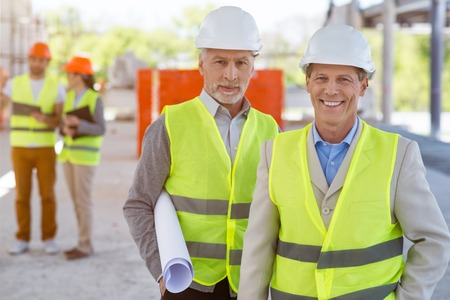 atmosphere construction: Being in a good mood. Cheerful and positive pair of architects standing and looking at a camera while holding a construction plan with a pair of another architects in a background Stock Photo