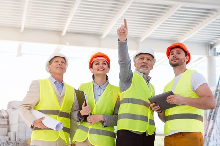 poking: Just right here.  Cheerful engineer standing and poking somewhere for his colleagues while showing and discussing new construction