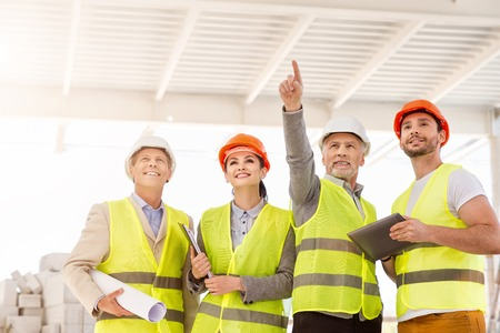poking: Our potentialities.  Confident and smiling engineer standing and poking somewhere for his delighted colleagues while showing and discussing new construction project