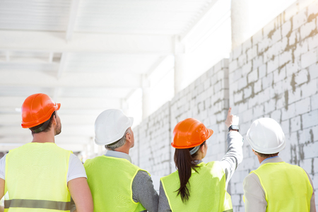 poking: Workers backs.  Positive female architect standing and poking somewhere for her cheerful colleagues while showing and talking about new brick walls