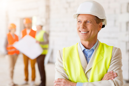 undone: Future perspectives. Happy and wistful man in a hardhat smiling and dreaming about future with his subordinates, which holding construction plans and standing in a background