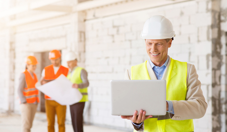 undone: Working moment. Cheerful and glad architect in a hardhat smiling and using a laptop with his colleagues, which holding a construction plan and standing in a background Stock Photo