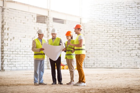 atmosphere construction: Construction process. Concentrated and confident team of architects standing together and looking very attentive at a building plans while holding a being on a construction