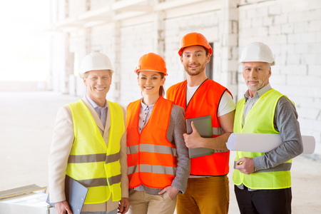 undone: Smiling team. Cheerful and content group of architects and engineers standing together near a new undone high building and holding construction plans, papers and a digital tablet Stock Photo