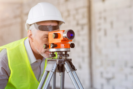 leveling instrument: Leveling.  Concentrated and wistful worker using a level standing in a new building