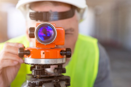 leveling instrument: Optical tool.  Busy and concentrated man using a theodolite-level standing in a new building