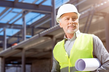 undone: Building steps.  Thoughtful and busy architect in helmet standing near new undone building and thinking about project Stock Photo