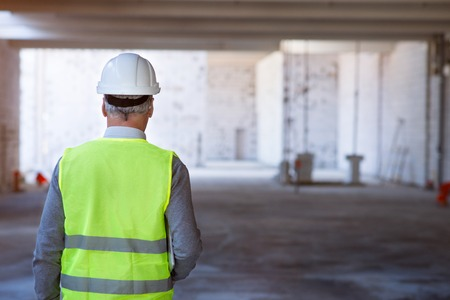 undone: Involved in work.  Busy architect in helmet going back while being in a a new undone building Stock Photo