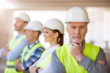 Secure of success.  Cheerful and confident architect standing near   his colleagues in a background while looking at a camera