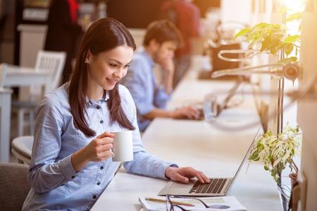 personas trabajando: Descansar un poco. Alegre hermosa mujer de tomar café encantados y trabajar en la computadora portátil mientras está descansando en el café