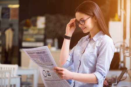 to be pleasant: Be informed. Pleasant delighted beautiful woman holding her glasses and reading newspaper while feeling happy