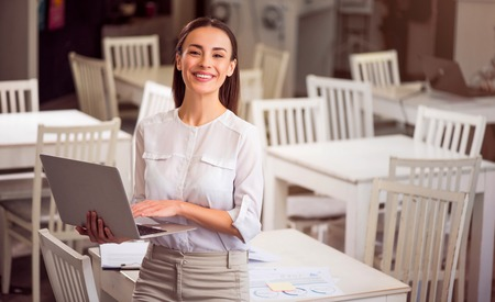 expressing joy: Express your emotions. Cheerful content smiling woman standing near table and expressing joy while holding laptop Stock Photo
