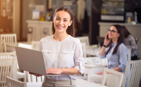 pleasant emotions: Full of emotions. Pleasant delighted overjoyed smiling woman holding laptop and expressing gladness while people sitting in the background
