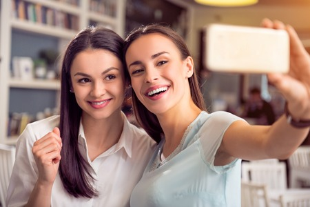 gladness: Say cheese. Cheerful  delighted woman holding cell phone and making selfie with her friend while evincing gladness