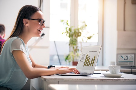 gladness: Full of joy. Joyful beautiful smiling woman sitting at the table and expressing gladness while working on the laptop Stock Photo