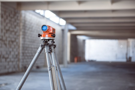 leveling instrument: Leveling. A theodolite-level standing in a new building may be used in construction works Stock Photo