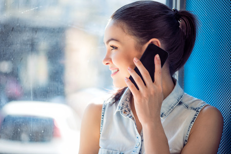 distance: Telecommunication. Positive and happy modern young woman talking on a smartphone and standing near a window while looking out of the window Stock Photo
