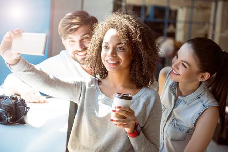 Selfie vrienden. Lachend en zeer positief moderne jonge vrouwen en man die samen in een cafe terwijl het drinken van koffie en het gebruiken hun smartphone om een foto te nemen selfie Stockfoto